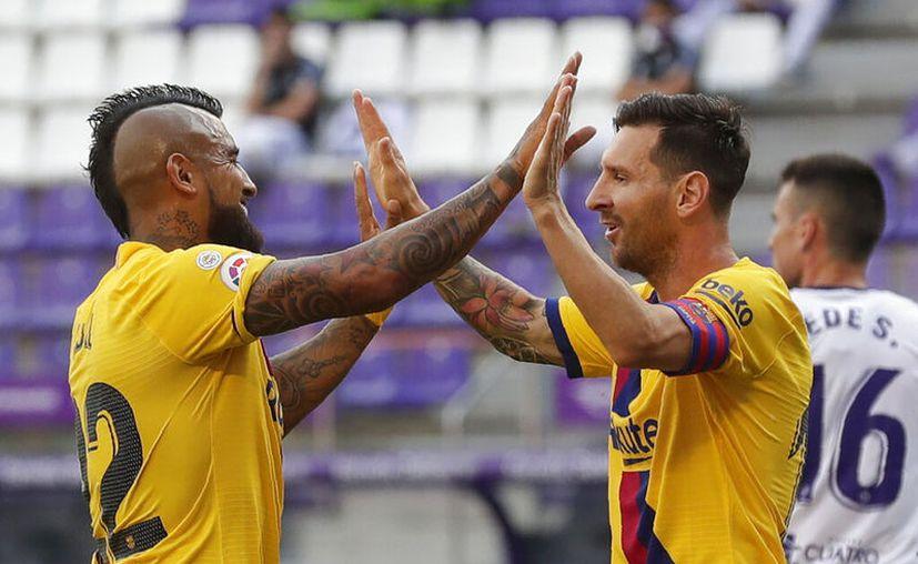 Arturo Vidal festeja su anotación con Lionel Messi. Barcelona se niega a tirar la toalla, aunque Real Madrid tiene ventaja de un punto en la carrera para cantar el Alirón. (Foto: AP)