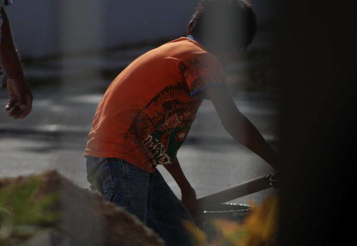 El menor ayuda a su papá en la albañilería. (Adrián Barreto/SIPSE)