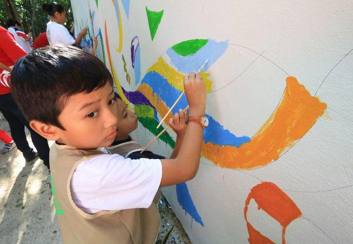 """Los niños pintaron el mural, bajo las instrucciones del artista local, Melchor Gaspar Mena Domínguez, conocido como """"Melhor"""". (Redacción/SIPSE)"""