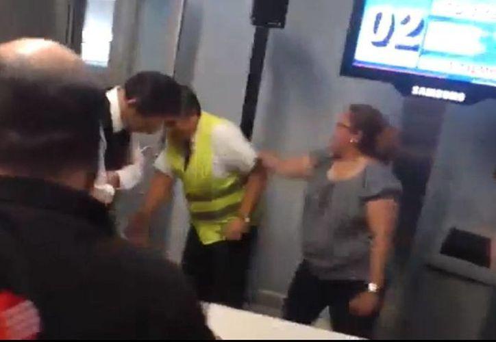 Momento en que una mujer agrede al empleador de la línea aérea. (Captura de pantalla del video subido a YouTube)