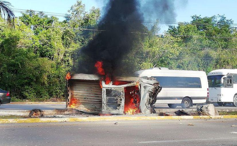 El vehículo se encuentra cubierto por las llamas en medio de la avenida. (Redacción/SIPSE)