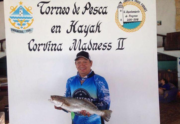 El presidente del club de Kayaqueros muestra la corvina más larga capturada este día, en el  torneo <i>Corvina Madness II</i>, realizado en Yucalpetén. El ejemplar midió 56 centímetros. (Gerardo Keb/SIPSE)