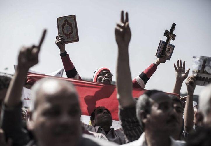 Un hombre egipcio sostiene un Corán en una mano, y un Cristo crucificado en la otra, en una manifestación celebrada en la plaza cairota de Tahrir, Egipto. (Archivo/EFE)