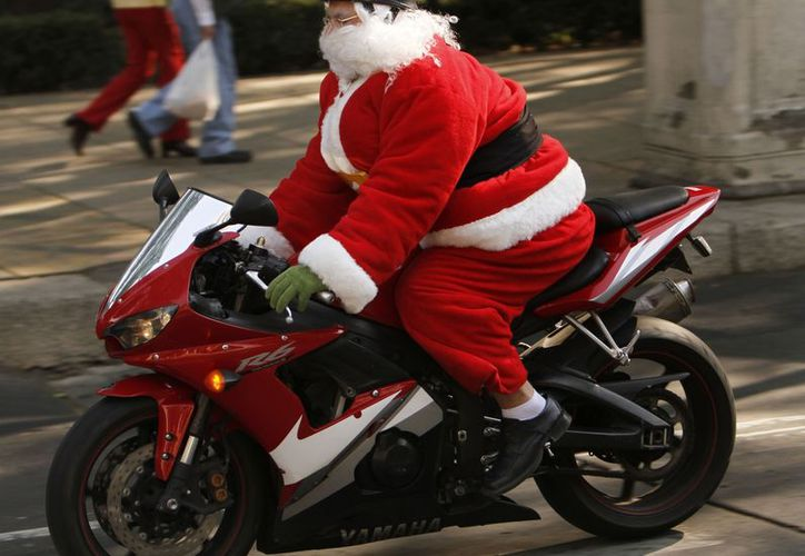 Un hombre disfrazado como Santa Claus es visto en motocicleta por la Ciudad de México. (Agencias)