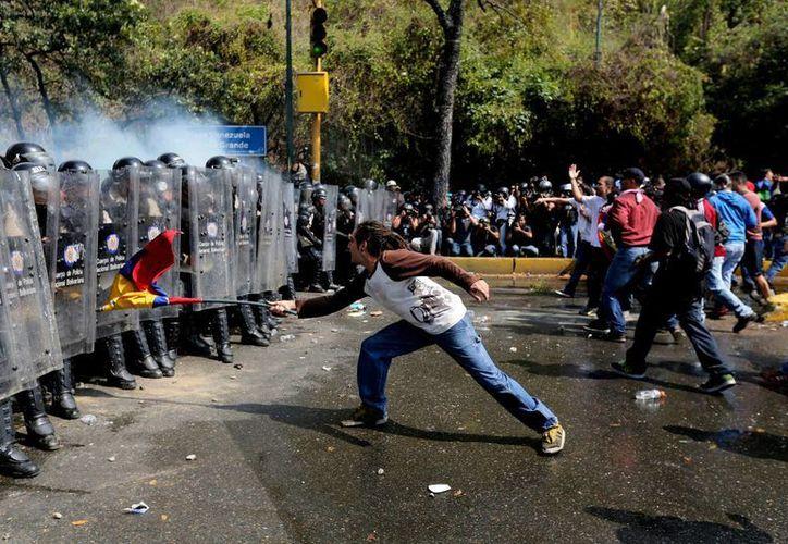 Un manifestante usa una bandera de Venezuela para atacar a una línea de agentes de la Policía Nacional Bolivariana con equipo antidisturbios, durante los enfrentamientos en una protesta contra el gobierno en Caracas, Venezuela. (Agencias)