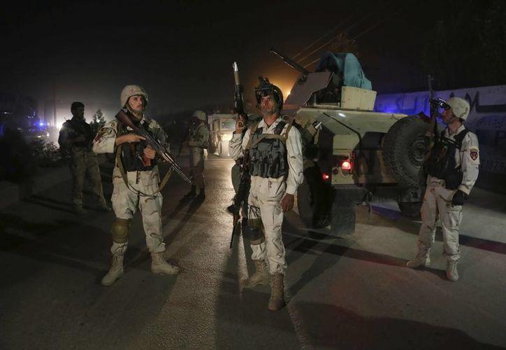 Varios miembros de las fuerzas de seguridad afganas toman posiciones en el lugar donde se produjo un ataque suicida. (EFE)