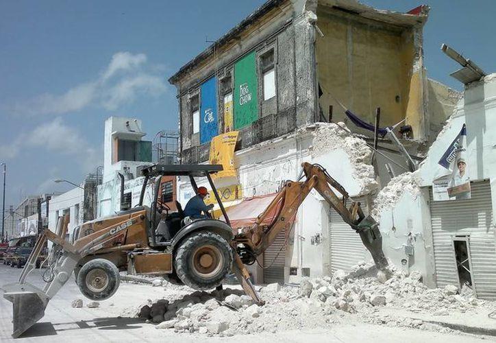 Trabajadores seguían retirando los escombros del predio que se derrumbó el jueves por la mañana. (Adán Escamilla/SIPSE)