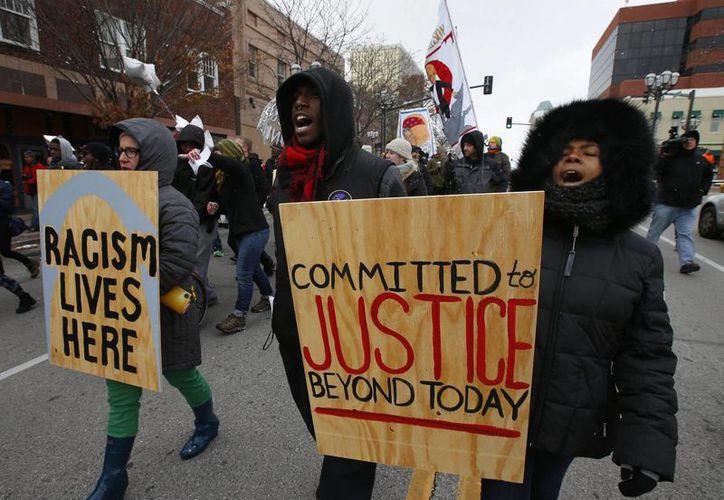Varios manifestantes marchan pidiendo justicia en el caso de Michael Brown, en Clayton, Misuri. (EFE)