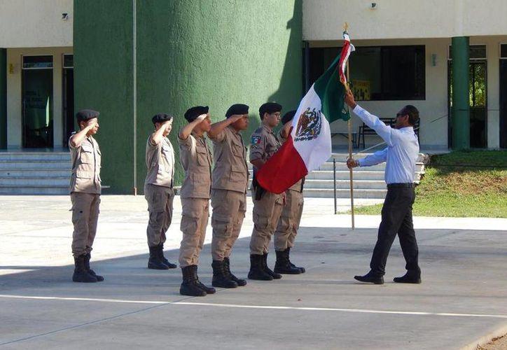 El director del plantel, José Gregorio Sánchez Díaz, entrega la bandera a la escolta de cadetes. (Cortesía. IMS)