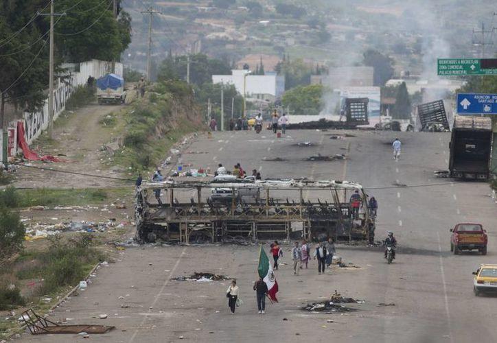 Las afectaciones por las protestas de la CNTE han alcanzado los sectores con mayor grado de pobreza y marginación en el estado de Oaxaca. Imagen de archivo de los enfrentamientos del domingo pasado entre policías e integrantes de la CNTE. (Agencias)