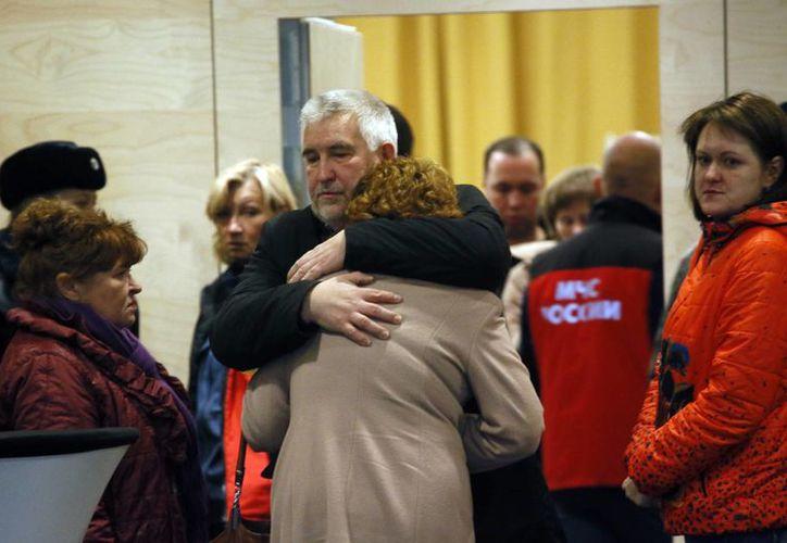 Los familiares y amigos de las personas del vuelo que se estrelló en Egipto se consuelan entre sí. (Agencias)