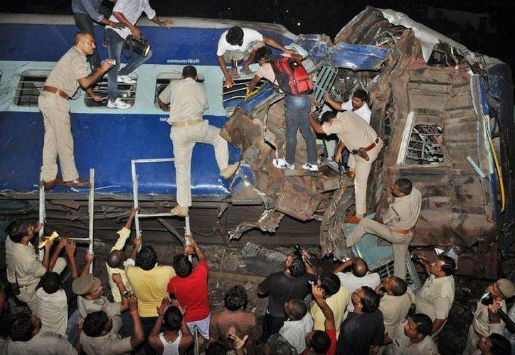 Policías y voluntarios intentan rescatar a los pasajeros del tren accidentado en India. Según las autoridades, fallecieron 14 personas y tras 45 resultaron heridas. (AP)