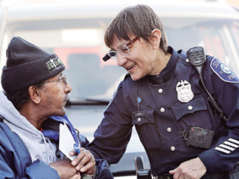 Seattle police officer Debra Pelich, right, wears a video camera on her eyeglasses as she talks with Alex Legesse before a small community gathering in Seattle. (AP)