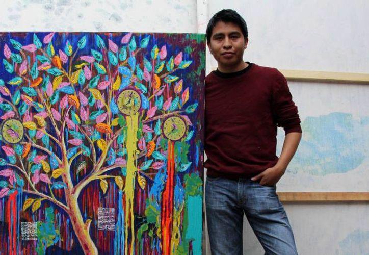 Carlos Bazán Ramos posa junto a una de sus obras. (Faride Cetina/SIPSE)