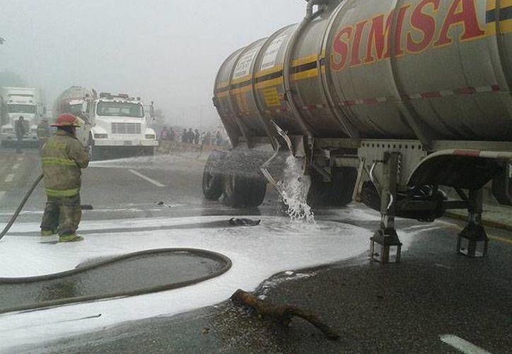 El percance se suscitó desde las tres de la madrugada, a la altura del kmo 8. En la foto, retiran el derrame de combustible en la vía. (Foto de Protección civil de Tabasco)