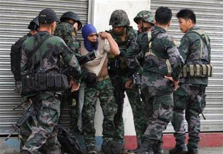 Varios soldados atienden a otro herido por un francotirador tras un enfrentamiento entre una patrulla naval filipina y presuntos insurgentes. (Agencias)