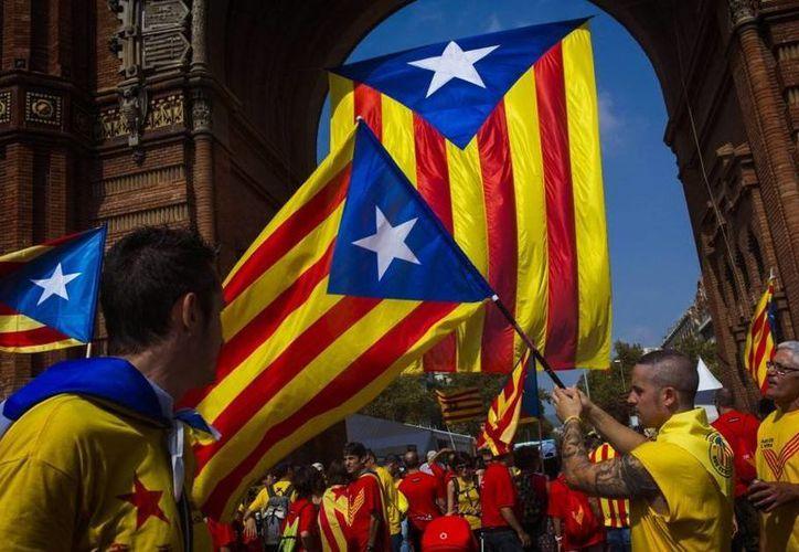 El gobierno de España se ha planteado bloquear por todos medios una posible declaración de independencia de Cataluña. En la imagen, simpatizantes de la proclamación del estado catalán ondean banderas de la región. (Archivo/AP)