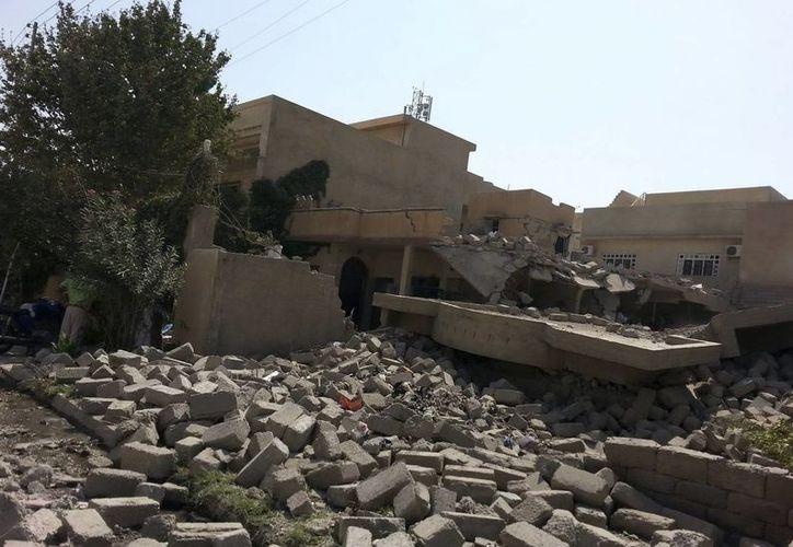 Varios iraquíes observan los restos de una casa destruida ayer en Mosul, norte de Irak, a consecuencia de bombardeos sobre las posiciones del Estado Islámico, que este jueves secuestraron a por lo menos 70 jóvenes. (EFE/Foto de contexto)