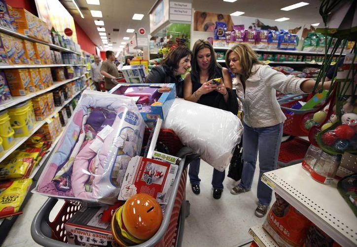 Tres mujeres consultan en un smartphone precios competitivos durante el Viernes Negro en un supermercado de South Portland, Maine, el 28 de noviembre de 2014. (Foto de archivo AP)