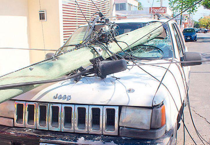 El chofer del vehículo de Conafor ingresaba al estacionamiento de una pizzería, cuando tiró el poste sobre la unidad de uno de los meseros.  (Foto: Redacción / SIPSE)