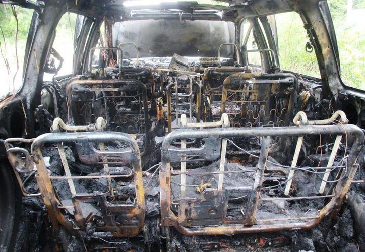 El taxi quedó completamente inservible tras el corto circuito que lo envolvió el llamas. (Redacción/SIPSE)