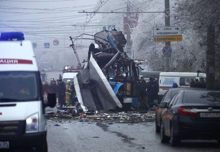 Policías y expertos en explosivos examinan el sitio de un atentado contra un autobús eléctrico en Volgogrado, Rusia. (Agencias)