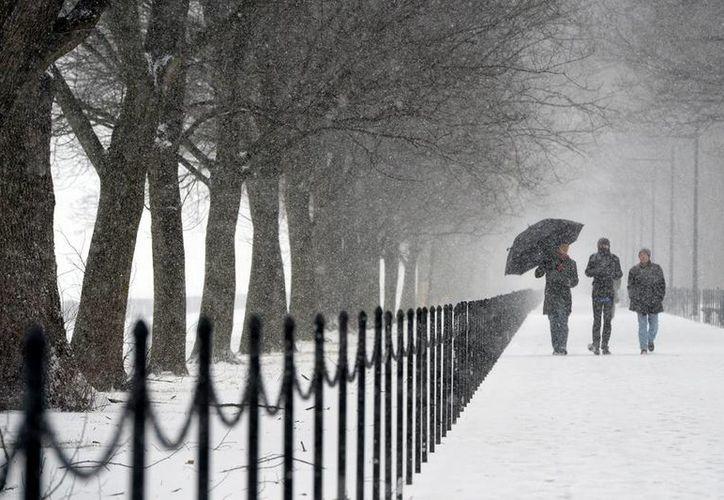 Tras la nieve, el frío cierra escuelas y oficinas en EU; en la imagen, unas personas caminan cerca al Monumento a Abraham Lincoln durante una tormenta de nieve en Washington DC. (Efe)