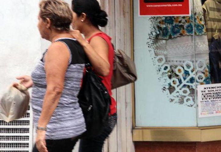 Dos mujeres caminan frente a un aparador donde se anuncia el Buen Fin que inicia el próximo 13 de noviembre. (Milenio Novedades)