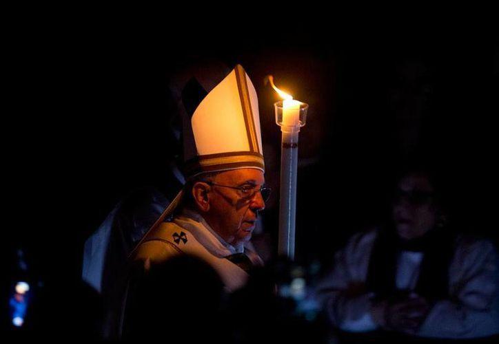 El Papa Francisco inició hoy la Vigilia Pascual: marcó un gran cirio pascual con una cruz y los símbolos de las letras griegas Alfa y Omega, luego con una oración hizo referencia a Jesús, principio y fin del universo. (AP)