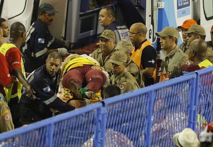 Bomberos trasladan a una persona herida enuna camilla durante las celebraciones del Carnaval en el Sambódromo. (AP/Leo Correa)