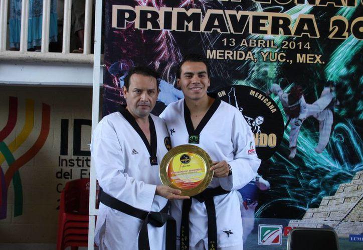 El campeón mundial Uriel Adriano recibe una distinción de manos de Rafael Vergara Briceño, director de la Agrupación 'Hermanos Vergara', en el marco del Campeonato Primavera. (Milenio Novedades)