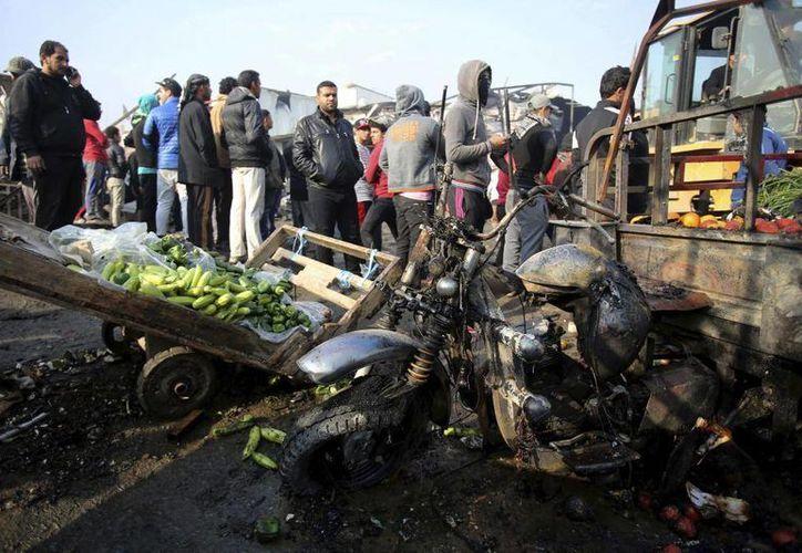 Ciudadanos inspeccionan el lugar donde estalló un coche bomba en un concurrido mercado al aire libre en el distrito de Sadr City, en Bagdad , Irak, el 8 de enero de 2017. La bomba mató a varios civiles, según un funcionario. (AP Foto/ Karim Kadim)