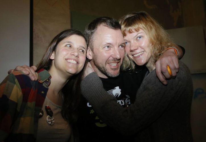 De izquierda a derecha, los activistas de Greenpeace Camila Speziale de Argentina, Phiip Ball de Gran Bretaña y Sini Saarela de Finlandia, posan para una foto durante su encuentro con residentes de San Petersburgo el 23 de diciembre. (Agencias)