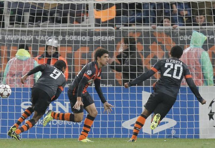 Taison (c), del Shaktar, celebra su gol con sus compañeros Douglas Costa (d) y Luiz Adriano. (Agencias)
