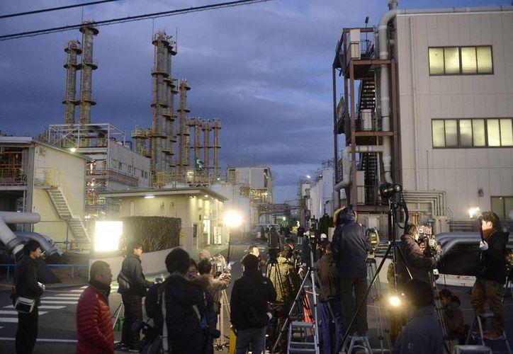 Periodistas hacen guardia a las afueras de la planta química de materiales de Mitsubishi, en Yokkaichi, Japon, donde se registró una explosión que mató a cinco personas. (Agencias)