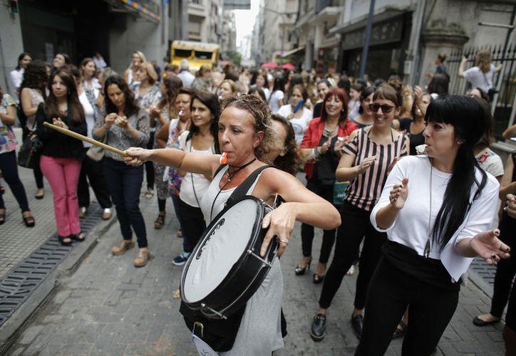 Una mujer toca un tambor durante una huelga de una hora para conmemorar el Día Internacional de la Mujer en Buenos Aires. (AP/Victor R. Caivano)