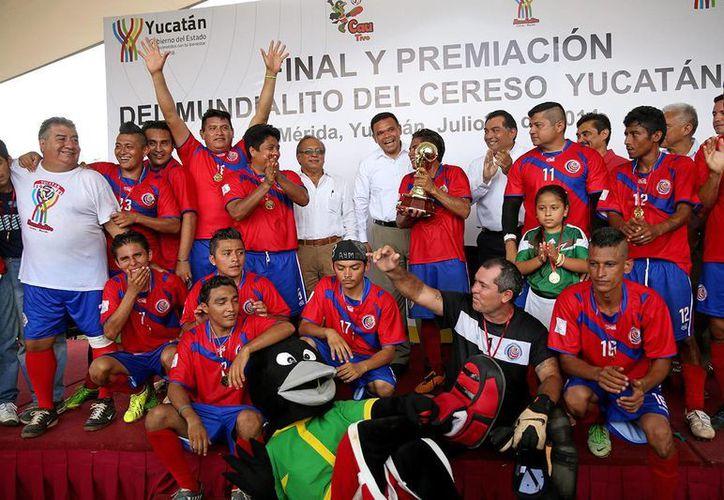 La 'selección tica', ganadora del Mundialito de Futbol Cereso 2014, se tomó la foto del recuerdo con el gobernador Rolando Zapata (c) y el trofeo FIFA. (SIPSE)