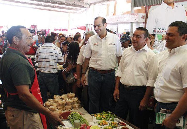 Acompañado de los candidatos por Umán, Felipe Cervera Hernández, aspirante priista a diputado federal por el V Distrito, saluda a un locatario del mercado municipal. (SIPSE)
