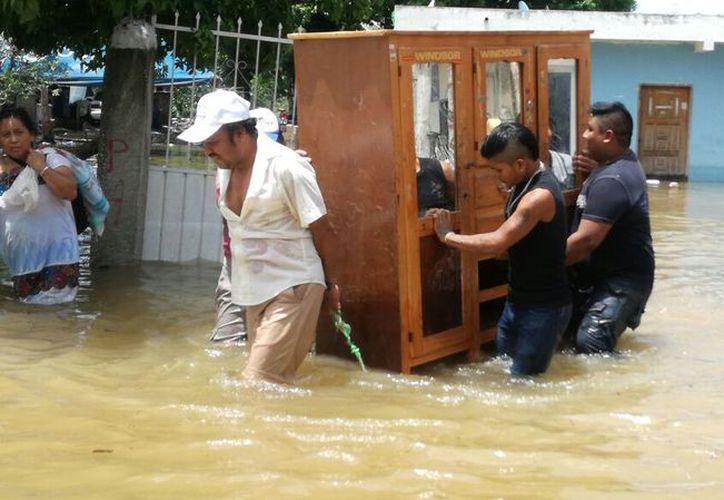 Hombres, las mujeres y los niños trabajan, a la par, para rescatar muebles, electrodomésticos. (Joel Zamora/SIPSE)