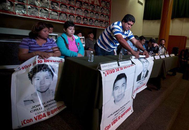 Padres de los normalistas desaparecidos sostienen algunas imagenes de los estudiantes durante una conferencia de prensa en la Ciudad de México. (Agencias)