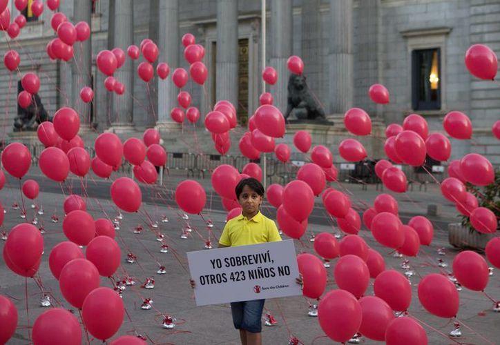 Zaid, un refugiado sirio de ocho años que ahora vive en España, sostiene un cartel que dice: 'Yo sobreviví, otros 423 niños no', ante el Congreso, en Madrid. (AP/Paul White)