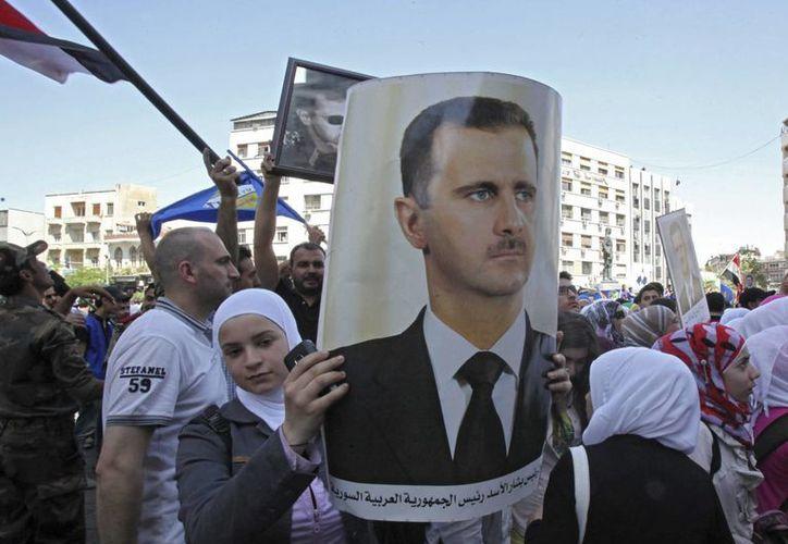 Miles de simpatizantes de Bashar Al Asad, algunos portando retratos suyos, participan en una concentración en Damasco para apoyar su candidatura presidencial. (EFE)