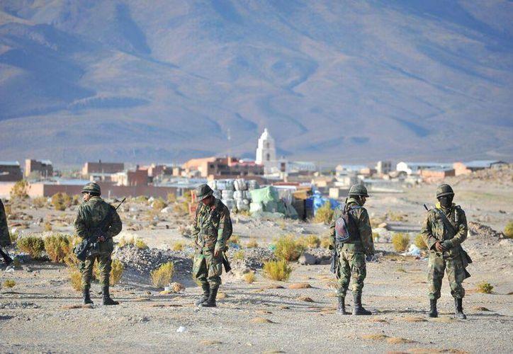 Imagen de un grupo de militares a un lado de los paquetes de contrabando que fueron depositados en la entrada del pueblo de Sabaya, ( APG Noticias)