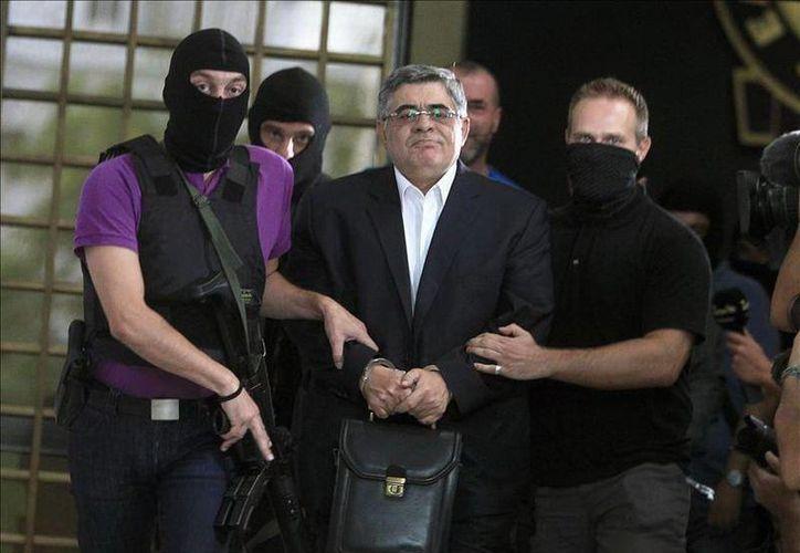El lider de Amanecer Dorado, Nikos Michaloliakos (c), es escoltado por policías afuera de la Jefatura de Policía de Atenas. ( EFE)