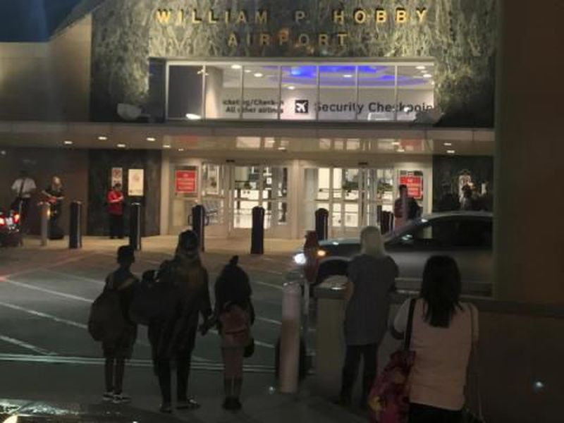People wait outside Houston's William P. Hobby Airport, after a toy grenade in a passenger's bag forced the shutdown of a security checkpoint.