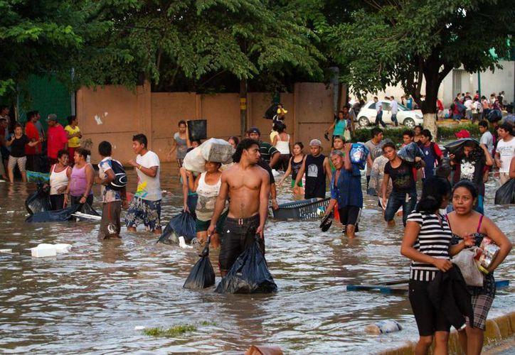 Algunas tiendas del puerto de Acapulco han sido abiertas a la fuerza por cientos de personas que se llevan electrodomésticos y comida. (Notimex)