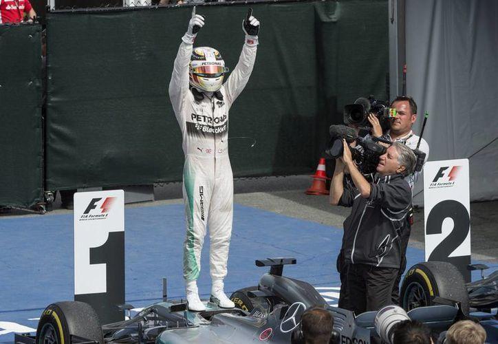 Lewis Hamilton ganó este domingo por cuarta vez el Gran Premio de Canadá y aumentó su ventaja  a 17 puntos sobre Nico Rosberg. En la imagen se observa al piloto británico celebrando por volver a lo más alto del podio. (AP)