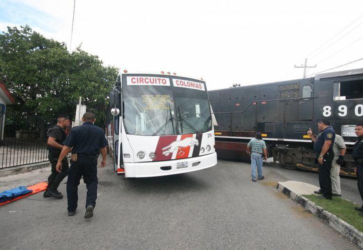 El autobús de la ruta Circuito Colonias falló en su intentó de ganarle al tren, en el crucero ferroviario que está a espaldas del hospital Juárez del IMSS en Mérida. (Jorge Sosa/SIPSE)