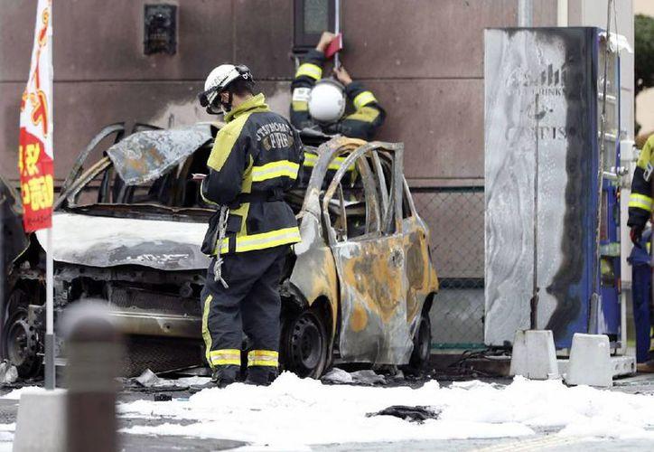 Dos bomberos en el sitio donde dos vehículos se quemaron en un estacionamiento en Utsunomiya, al norte de Tokio, el domingo 23 de octubre de 2016. (Yukie Nishizawa/Kyodo News vía AP)