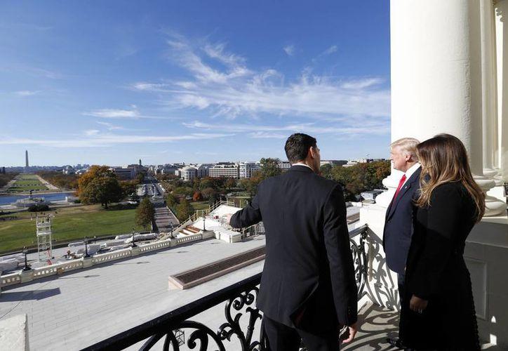 Imagen del presidente electo Donald Trump acompañado de esposa Melania y el presidente de la Cámara, Paul Ryan, desde el Balcón del Capitolio en Washington, este jueves. (AP/Alex Brandon)